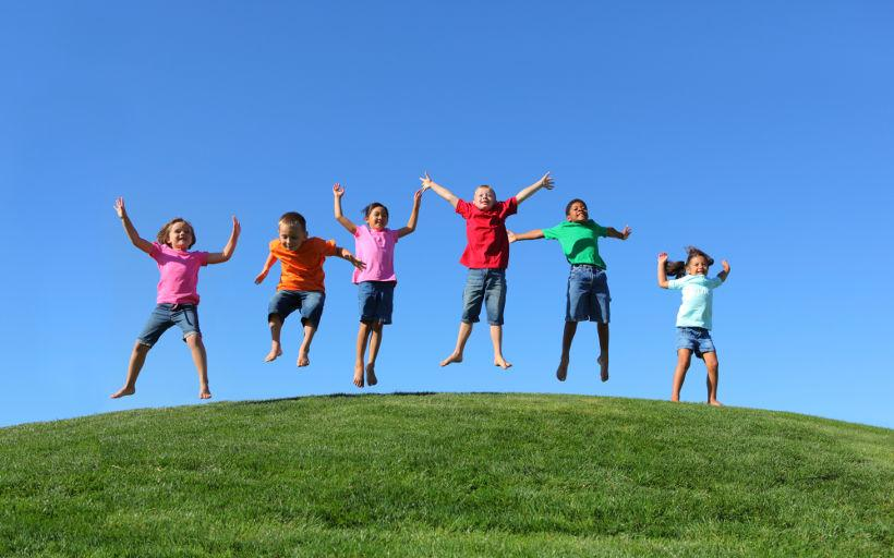 Children jump up a hill